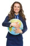 Glimlachende bedrijfsvrouw die aardebol koesteren Royalty-vrije Stock Fotografie