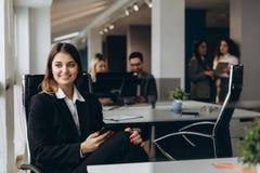 Glimlachende bedrijfsvrouw die celtelefoon met collega's op achtergrond in bureau met behulp van stock afbeeldingen