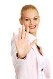 Glimlachende bedrijfsvrouw die eindeteken tonen aan de camera Royalty-vrije Stock Foto's