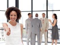 Glimlachende bedrijfsvrouw die teamgeest toont Stock Foto