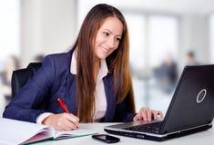 Glimlachende bedrijfsvrouw in haar bureau Stock Foto