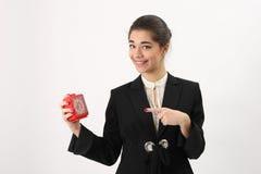 Glimlachende bedrijfsvrouw met alarm in zijn hand stock foto's