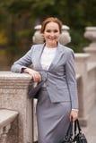 Glimlachende bedrijfsvrouwen in grijs kostuum met handtas Stock Foto's