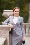Glimlachende bedrijfsvrouwen in grijs kostuum met handtas Stock Afbeeldingen