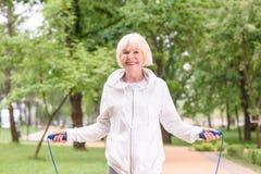 glimlachende bejaarde sportvrouw met springtouw royalty-vrije stock foto's