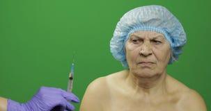Glimlachende bejaarde vrouwelijke dame in beschermende die hoed van spuit met geneesmiddelen wordt doen schrikken stock foto