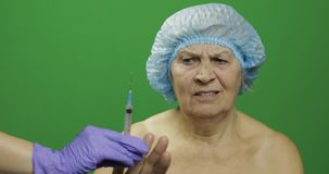 Glimlachende bejaarde vrouwelijke dame in beschermende die hoed van spuit met geneesmiddelen wordt doen schrikken stock afbeelding