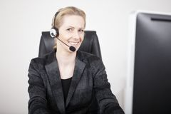 Glimlachende Bestuurster die Hoofdtelefoon dragen op haar Kantoor Stock Afbeelding
