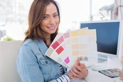 Glimlachende binnenlandse ontwerper die kleurensteekproeven steunen stock fotografie