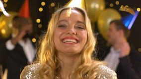 Glimlachende blije dame die op confettien blazen en aan camera, verjaardagspartij kijken stock footage