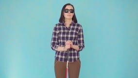 Glimlachende blinde of met gezichtsstoornissen jonge vrouw met glazen en een riet stock footage