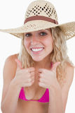 Glimlachende blonde tiener die haar twee duimen toont Stock Afbeelding