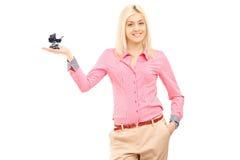 Glimlachende blonde vrouw die een kinderwagen in haar hand houden Stock Afbeelding