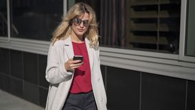 Glimlachende blonde vrouw in zonnebril die en telefoon lopen bekijken stock footage