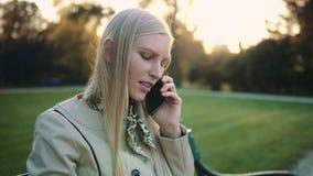 Glimlachende blondevrouw met van tabletcomputer en cellphone zitting op parkbank stock video