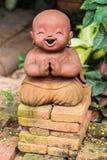 Glimlachende boeddhistische die beginner van klei, Thaise stijl wordt gemaakt stock afbeelding