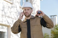 Glimlachende bouwer in beschermingsmateriaal op telefoon Stock Fotografie