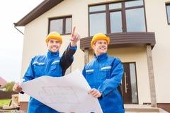Glimlachende bouwers die met blauwdruk vinger richten Stock Foto