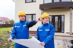 Glimlachende bouwers die met blauwdruk vinger richten Royalty-vrije Stock Foto's