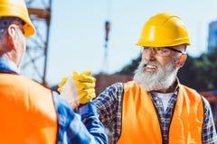 Glimlachende bouwvakker in beschermende eenvormige het schudden handen stock foto's