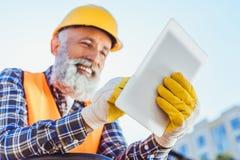 Glimlachende bouwvakker in het weerspiegelende vest en bouwvakker gebruiken stock afbeeldingen