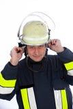 Glimlachende brandweerman die zijn helm dragen Royalty-vrije Stock Fotografie