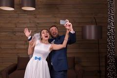 Glimlachende bruid en bruidegom die selfie op telefoon maken Stock Fotografie