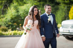 Glimlachende bruid met een boeket en gelukkige bruidegom die aan wedd lopen Stock Afbeelding