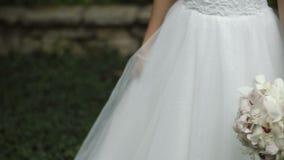 Glimlachende bruid in perfecte huwelijkskleding met mooi boeket van witte bloemen stock video