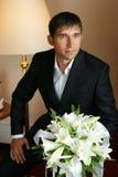 Glimlachende Bruidegom die een boeket houdt Royalty-vrije Stock Foto's