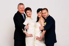 Glimlachende bruidegom en bruid met ouders stock foto's