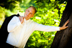 Glimlachende Bruidegom en een grote boom Stock Afbeelding