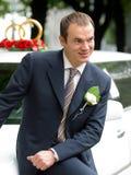 Glimlachende Bruidegom op de limousine van de huwelijksAuto stock fotografie