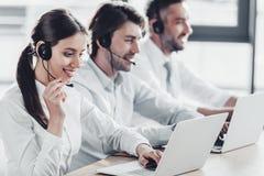 glimlachende call centremanagers in witte overhemden die terwijl het zitten in rij samenwerken royalty-vrije stock afbeeldingen