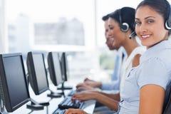 Glimlachende call centrewerknemer die camera bekijken Stock Afbeelding