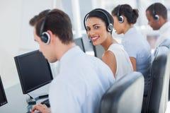 Glimlachende call centrewerknemer die over schouder kijken Stock Foto's