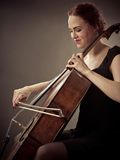 Glimlachende Cellist die haar oude cello spelen Royalty-vrije Stock Foto