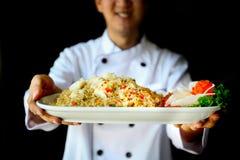 Glimlachende Chef-kok die trots krab gebraden rijst op donkere dramatische achtergrond voorstellen royalty-vrije stock foto's