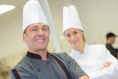 Glimlachende chef-kok en commischef-kok stock foto