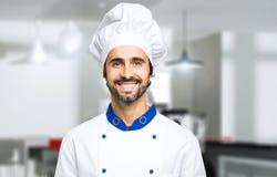 Glimlachende chef-kok in zijn keuken Royalty-vrije Stock Afbeelding