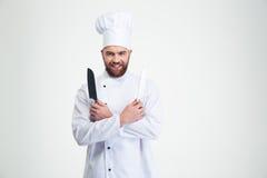 Glimlachende chef-kokkok die twee knifes houden Royalty-vrije Stock Afbeeldingen