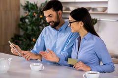 Glimlachende collega's die tablet in de keuken gebruiken stock foto