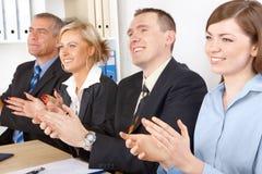 Glimlachende commerciële groep die handen slaat stock afbeelding