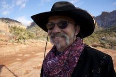 Glimlachende cowboy met zonnebril in rode rotsen Royalty-vrije Stock Afbeeldingen