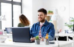 Glimlachende creatieve mens met laptop die op kantoor werken stock fotografie