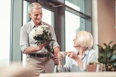 Glimlachende dame die bloemen van een mens ontvangen royalty-vrije stock foto