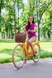 Glimlachende dame die een heldere gele fiets op recreatief gebied berijden stock afbeeldingen