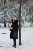 Glimlachende dame in een bontjas in het de winterbos stock fotografie