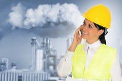 Glimlachende dameingenieur die op de telefoon en de fabriek in Th spreken royalty-vrije stock foto's