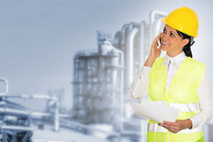 Glimlachende dameingenieur die op de telefoon en de fabriek in Th spreken Royalty-vrije Stock Afbeelding